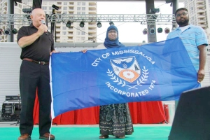From Left to Right: Mississauga Ward 6 Councillor Ron Starr presents the flag of the city to MuslimFest's Rina Rahman, artistic development & management and legal advisor, MuslimFest and Saffraz Khan, event director, MuslimFest 2013.