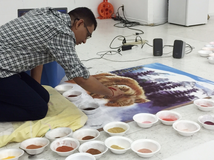 Canadian artist Praksh Shirke fills in the snout of a grizzly bear with coloured sand. Prakash has taken the ancient Indian art of Rangoli and transformed it.