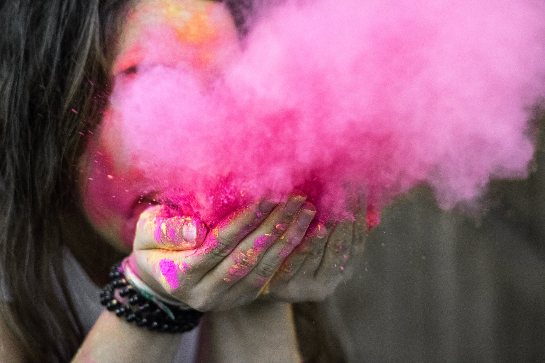 Woman blows a plume of pink colour