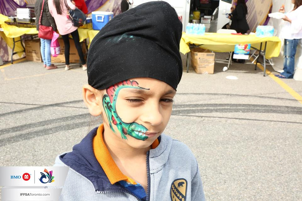 A young Sikh boy wearing a turban has his face painted.