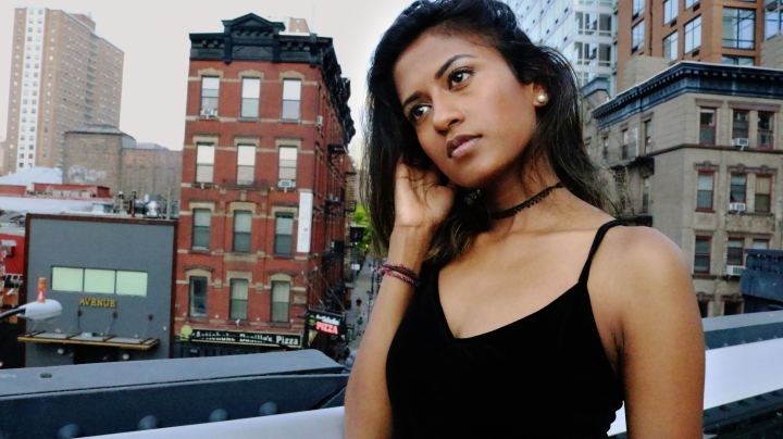 Photo of Tamil rapper set against the backdrop of high-rise buildings