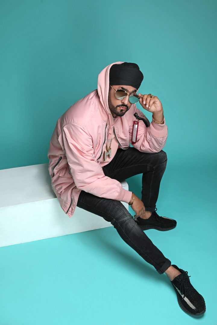 Manjeet Rai aka Manj Musik sits on a white platform against a green backdrop.