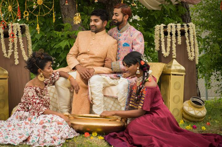 Two men wearing traditional Indian wedding clothes surrounded by two women wearing flowers in their hair