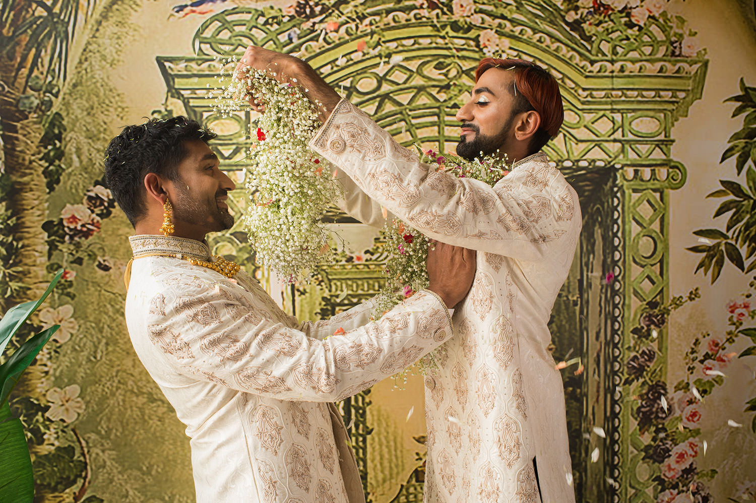 Two male members of the South Asian LGBTQ community exchange traditional flower garlands as part of a photo shoot.
