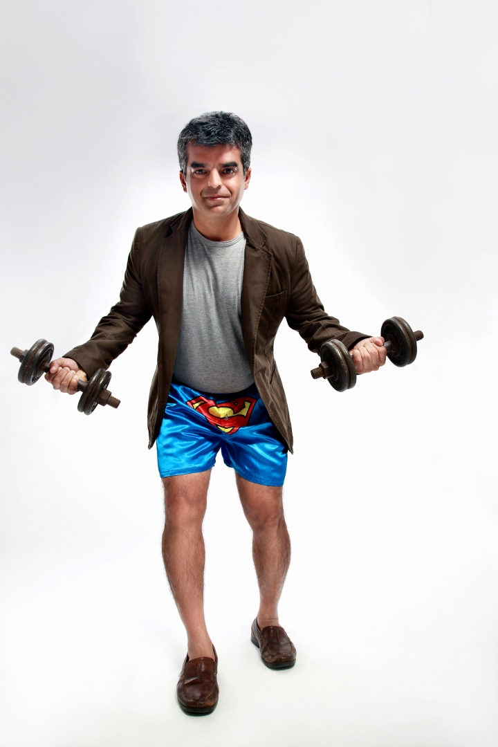 Atul Khatri, wearing underwear with a Superman logo and carrying dumbbells