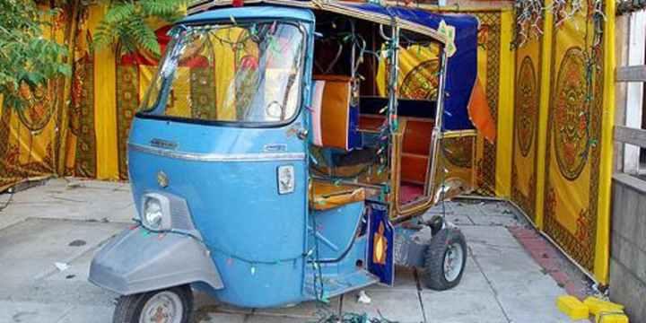 A photo of a blue autorickshaw